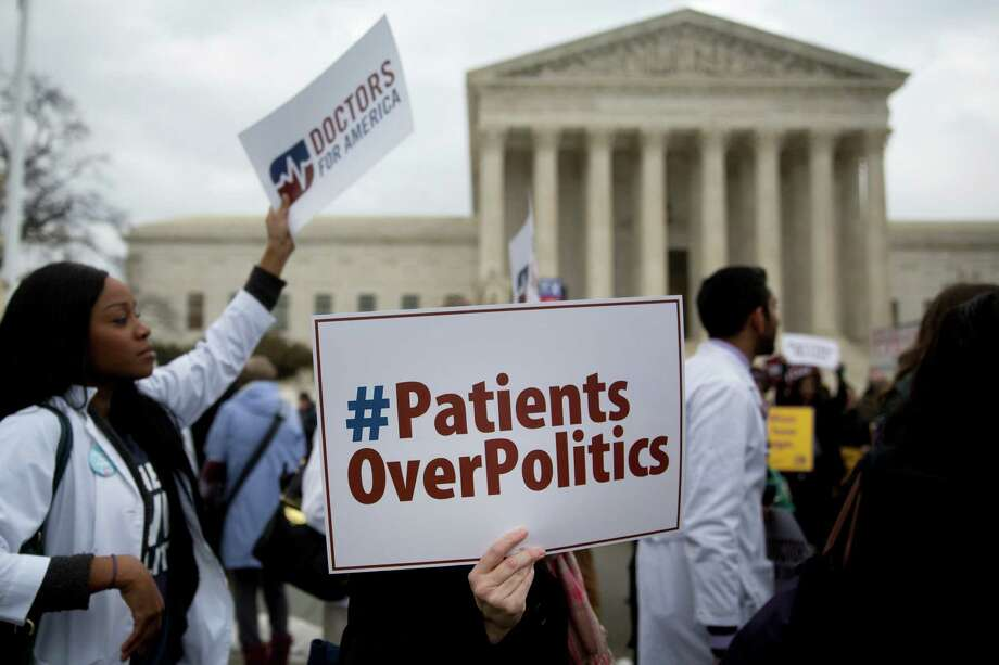 Demonstrators from Doctors for America in support of U.S. President Barack Obama's health-care law, Obamacare, hold signs while marching in front of the U.S. Supreme Court last week. A ruling is expected this summer. Photo: Andrew Harrer /Bloomberg / © 2015 Bloomberg Finance LP