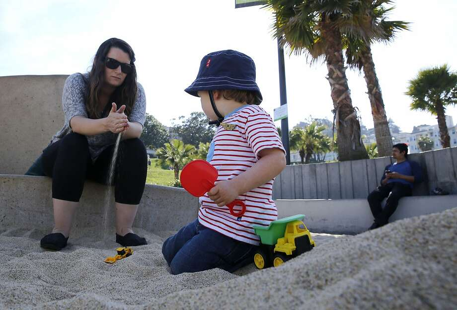 Nanny Carly Studzinski cares for Sebastian Berle-Smith at Dolores Park in San Francisco. As families go on summer vacation, more are bringing their nannies along. Photo: Liz Hafalia, The Chronicle