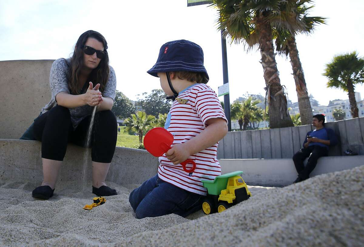 Nanny Carly Studzinski feels the sand as Sebastian Berle-Smith, 2 years old, plays at the sandbox filled with new sand in the children's playground at Dolores Park in San Francisco, California on Monday, March 9, 2015. Twenty tons of sand replaced polluted sand by vandals breaking bottles a few weeks ago