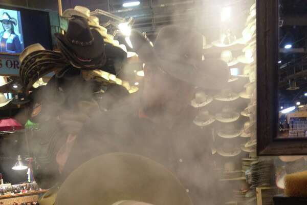 """Hat steamer Cowboy hats off the assembly line don't look the iconic Western ware we know; they're flat-brimmed and totally dome-topped. So hat artisans at the rodeo set up shop to give their products the characteristic shape, and the key contraption is a steam machine. """"Any hat store has this same kind of setup,"""" said Marcus Williams with Heads or Tails Hats as he points to the steam-spewing work table where he custom shapes hats for customers. """"But this head's been remanufactured to put out a lot more steam."""" The devices--they use three of them--are actually commercial jewelry cleaners (about $1,500 new), but with some modification they work great for steaming hats. Normally the hats are stiff, but they get pliable with a little hot vapor, allowing the artist to give the perfect shape for the customer's head and style. It's a trick to get right, but Williams has been shaping hats for about 16 years. """"If you do enough of them, you'll get the hang of it,"""" he said. """"It's just repetition, like anything."""" Pictured: Marcus Williams steams a hat."""