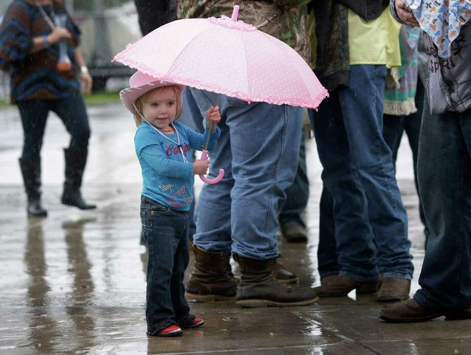 Zelda Thompson, 2, of Pasadena waits in the rain to entry NRG Stadium for RodeoHouston at the Houston Livestock Show and Rodeo in Monday, March 9, 2015, in Houston. Photo: Melissa Phillip, Houston Chronicle / © 2014  Houston Chronicle