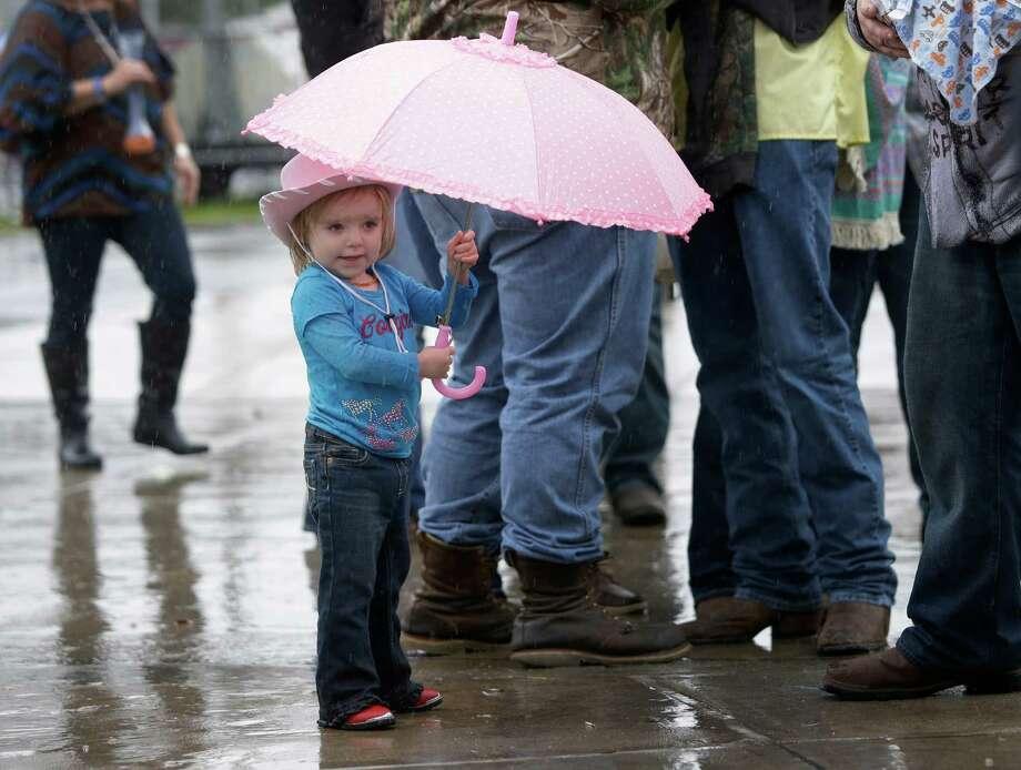 Zelda Thompson, 2, of Pasadena waits in the rain to entry NRG Stadium for RodeoHouston at the Houston Livestock Show and Rodeo in Monday, March 9, 2015, in Houston. Photo: Melissa Phillip, Houston Chronicle / © 2014  Houston Chronicle