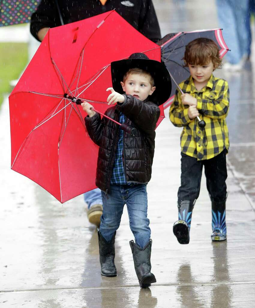 Five-year-olds Luke Spears, left, and his friend Eli Riley, right, walk outside during the Houston Livestock Show and Rodeo at NRG Park Monday, March 9, 2015, in Houston.