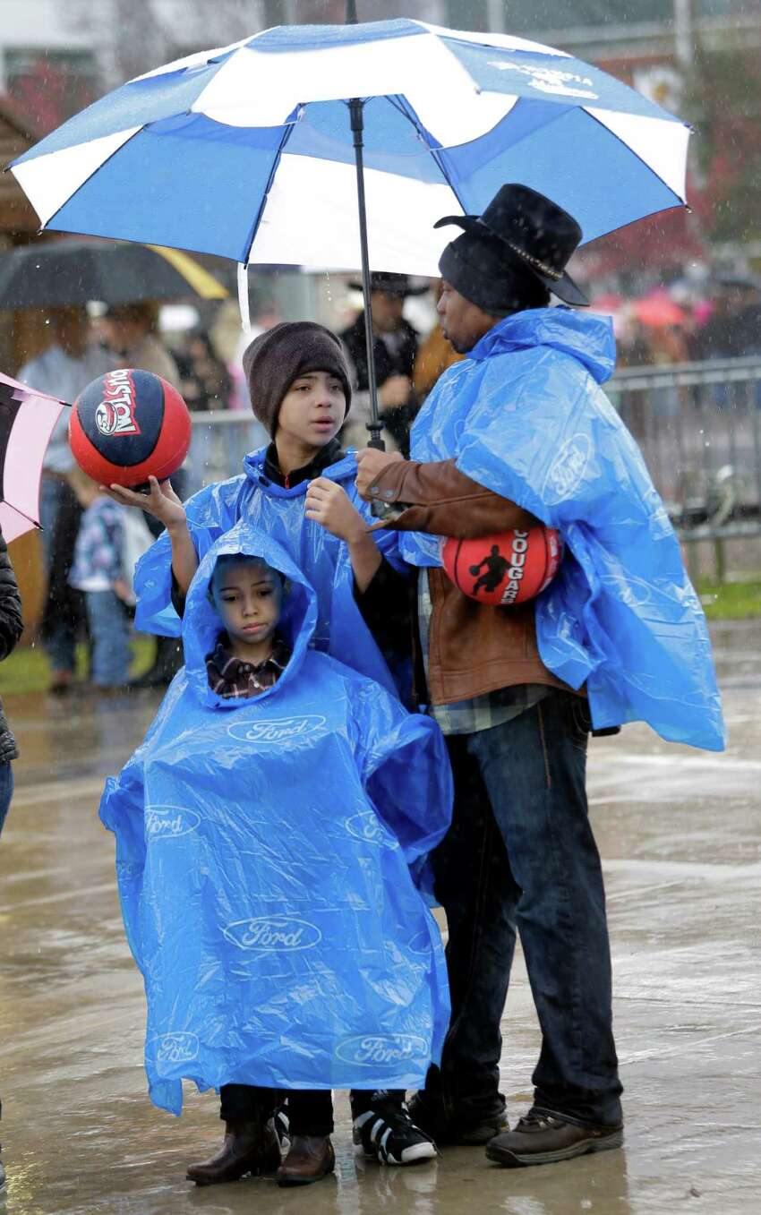 David Daniel of Houston and his sons, Jaxon, 7, and Jade, 13, wait in line in the rain to entry NRG Stadium for RodeoHouston at the Houston Livestock Show and Rodeo in Monday, March 9, 2015, in Houston. They won a few carnival prizes on the Midway.
