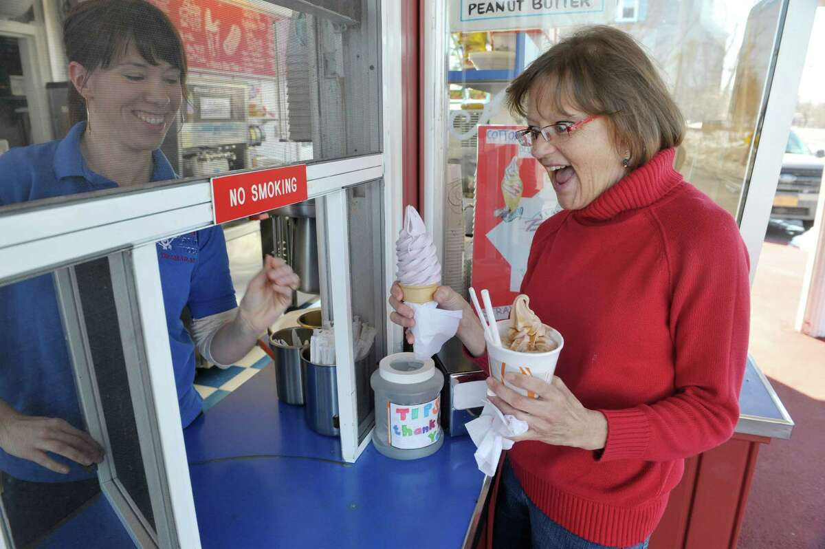 Kim Sheldon of Albany gets an ice cream cone and a shake from Jaime Greenfield at Jim's Tastee Freez on Monday, March 9, 2015, in Delmar, N.Y. The ice cream stand opened on Saturday to start their season. (Paul Buckowski / Times Union)