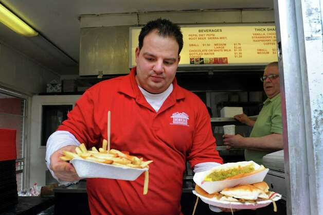 Owner Albert Deeb, center, delivers lunch through the service window on Wednesday, March 19, 2014, at Jack's Drive In in Wynantskill, N.Y. The drive-in's opening signals the start of spring. At right is employee Phil Coli. (Cindy Schultz / Times Union) Photo: Cindy Schultz / 00026205A