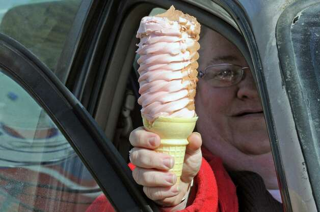 Debbie Plante holds up the first cone of the year at The Snowman on opening day Friday March 7, 2014 in Troy, N.Y. her and her husband Jim Plante arrived early to wait in line to be the first customer of the season.(Michael P. Farrell/Times Union) Photo: Michael P. Farrell / 00026046A