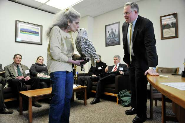 Wendy Hall with Adirondack Wildlife Refuge and Rehab Center in Wilmington gives Cara, a snowy owl, a kiss as Assembly member Dan Stec, right, looks on at the Legislative Office Building on Monday, March 9, 2015, in Albany, N.Y.  Hall and members of Audubon New York were visiting legislators to stress the importance of increasing funding in the budget for the Environmental Protection Fund.  Cara was found injured in Malone and her wing can not be repaired because of where the break is.  People from about 70 organizations and businesses who support increasing the Environmental Protection Fund in the State Budget were in Albany on Monday talking to legislators.    (Paul Buckowski / Times Union) Photo: PAUL BUCKOWSKI / 00030940A