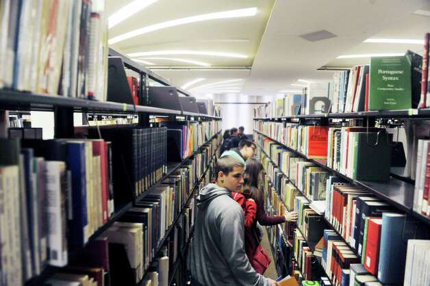 Schenectady High School student Cody Peek, foreground, and other area high school students look for a specific book as they take part in a scavenger hunt during Spanish Heritage Day at the University at Albany on Monday, March 9, 2015, in Albany, N.Y. The event which is hosted by the Department of Languages, Literatures & Cultures, gives high school students total immersion in a language for the day. (Paul Buckowski / Times Union) Photo: PAUL BUCKOWSKI / 00030913A