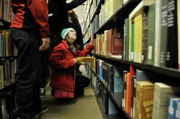 Ichabod Crane High School student Samantha Hesler and other area high school students look for a specific book as they take part in a scavenger hunt during Spanish Heritage Day at the University at Albany on Monday, March 9, 2015, in Albany, N.Y. The event which is hosted by the Department of Languages, Literatures & Cultures, gives high school students total immersion in a language for the day. (Paul Buckowski / Times Union) Photo: PAUL BUCKOWSKI / 00030913A