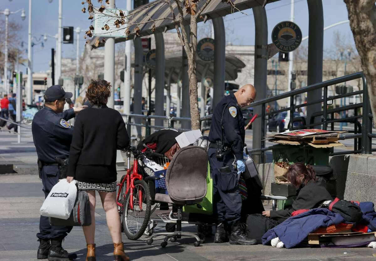 Police question two homeless women from Missouri who set up camp on a MUNI boarding ramp in the plaza between Market Street and the Ferry building. Homeless encampments are still prevalent in San Francisco, Calif. and their locations are becoming more apparent.