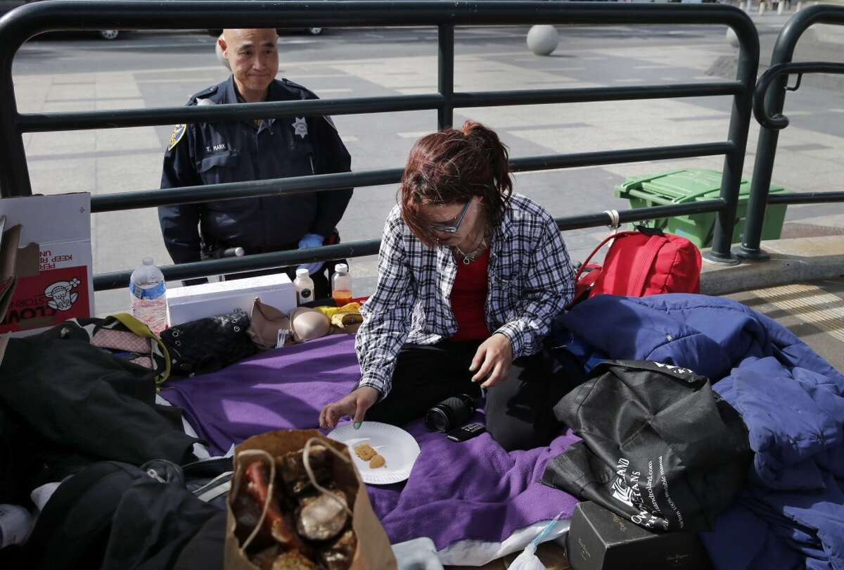 A police officer removes a homeless woman named Rose, from Missouri, who has set up camp on a MUNI boarding ramp Monday March 2, 2015. Homeless encampments are still prevalent in San Francisco, Calif. and their locations are becoming more apparent.