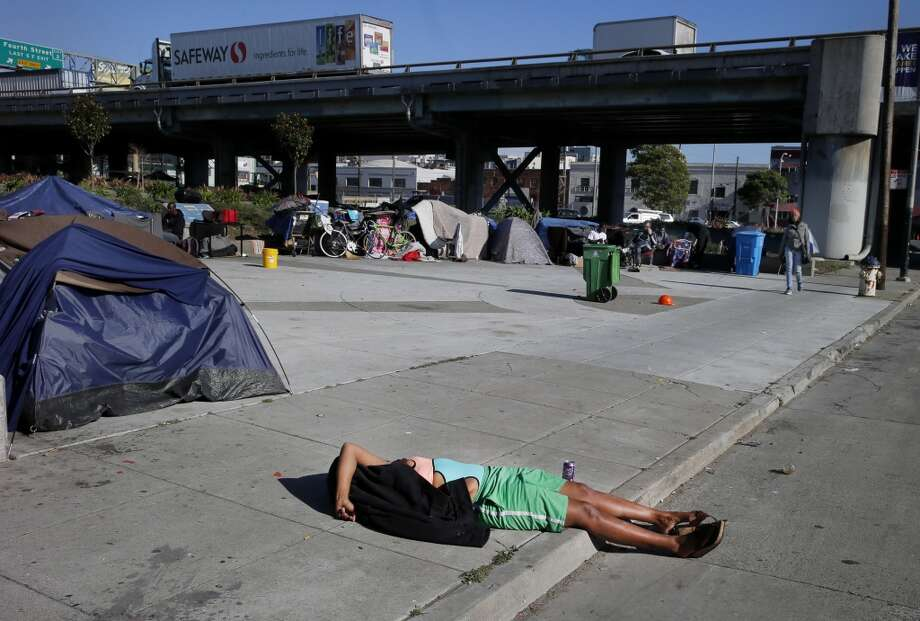 A homeless woman from the encampment on 5th Street near the Bay Bridge entrance lay in the sidewalk and street Tuesday March 3, 2015. Homeless encampments are still prevalent in San Francisco, Calif. and their locations are becoming more apparent. Photo: The Chronicle