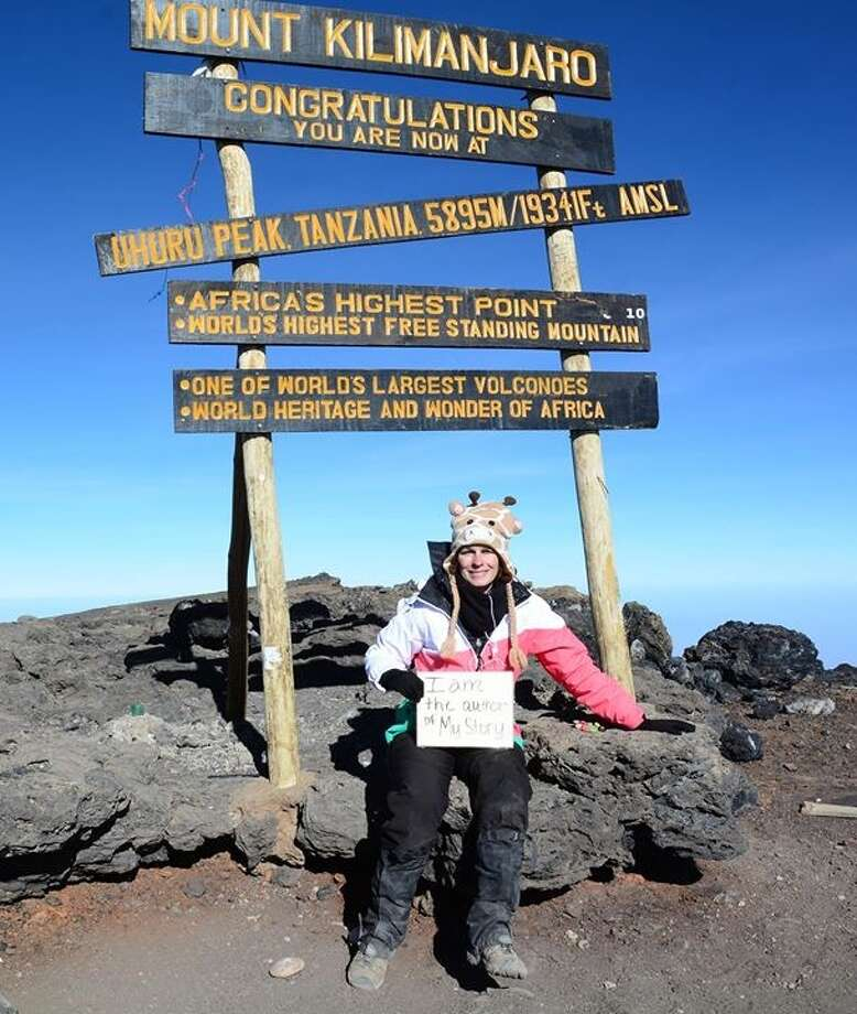 Cindy Greene of Lumberton sits beneath a sign at the top of Mount Kilimanjaro in the east African country of Tanzania. It is volcano with two extinct cones and one dormant cone, Kibo, which still leaks some gases. Uhuru Peak is the mountain's tallest point — 19,341 feet average mean sea level — on Kibo. The sign Greene holds reads 'I am the author of my story.'  Photo: Cindy Greene