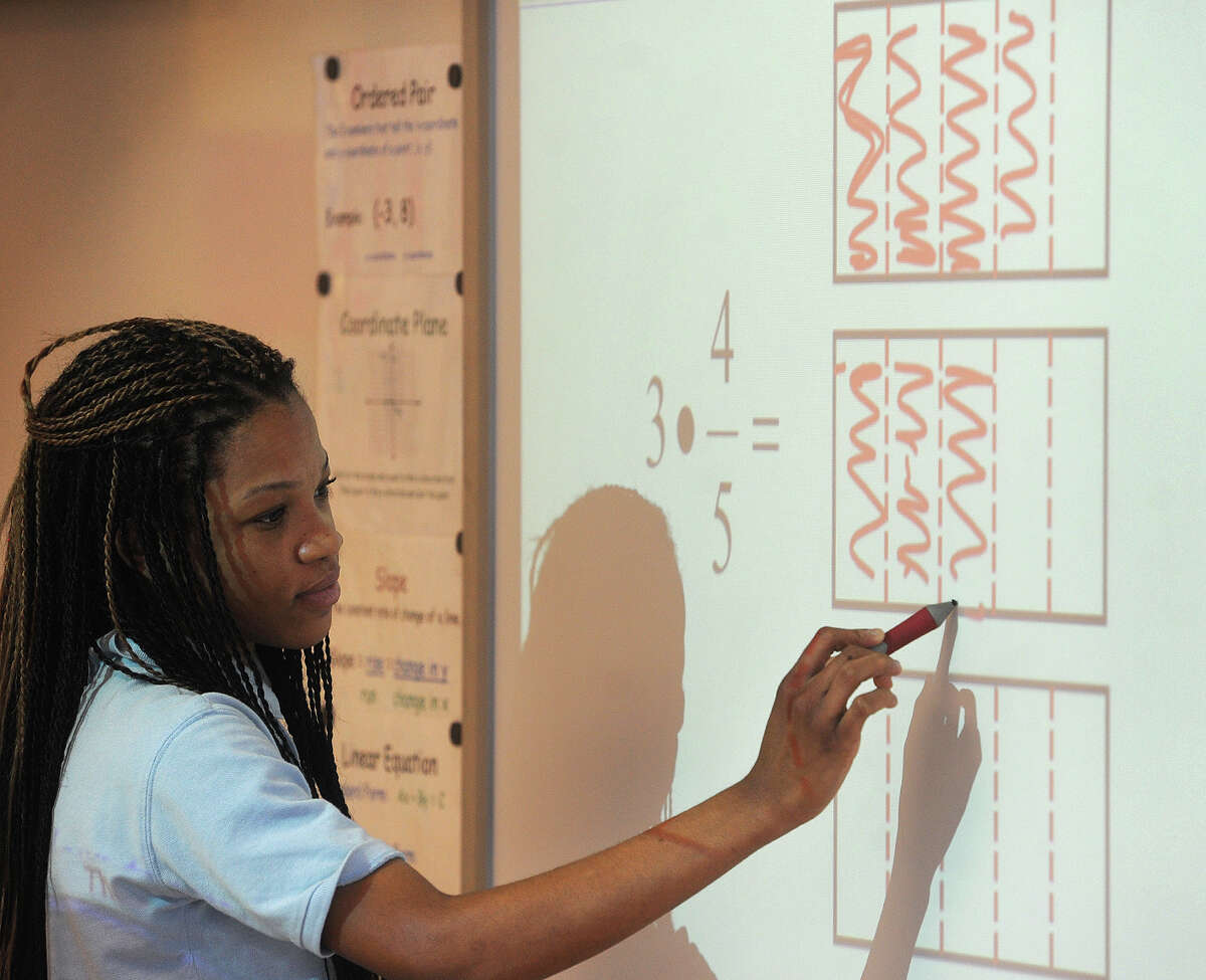 Eighth grader Judi-Ann Freemantle, 13, works out a fraction multiplication problem using an area model at Jettie Tisdale School in Bridgeport, Conn. on Tuesday, March 10, 2015.