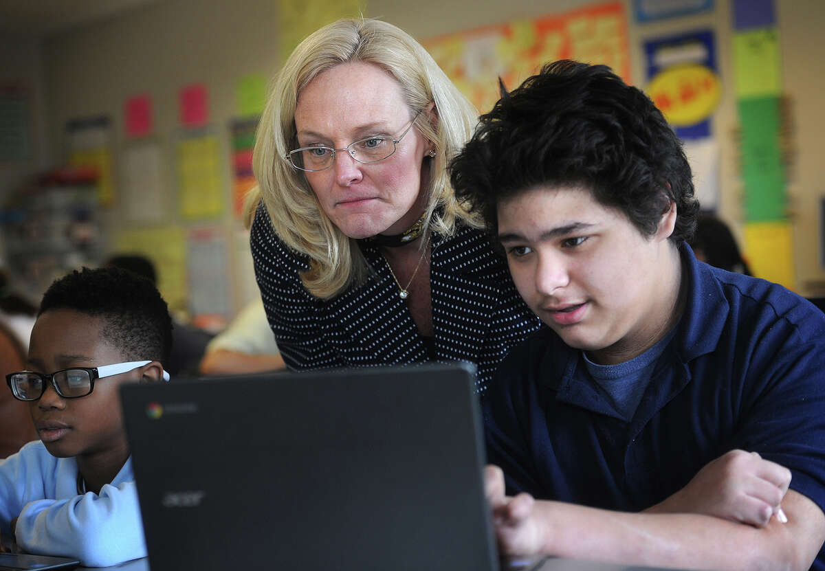 Sixth grader teacher Kathy Cunningham and student Jayvan Marrero, 12, review the format of the new common core standardized test, which will be taken online, at Jettie Tisdale School in Bridgeport, Conn. on Tuesday, March 10, 2015.