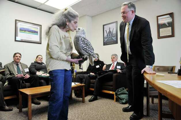 Wendy Hall with Adirondack Wildlife Refuge and Rehab Center in Wilmington gives Cara, a snowy owl, a kiss as Assembly member Dan Stec, right, looks on at the Legislative Office Building on Monday, March 9, 2015, in Albany, N.Y.  Hall and members of Audubon New York were visiting legislators to stress the importance of increasing funding in the budget for the Environmental Protection Fund.  Cara was found injured in Malone and her wing can not be repaired because of where the break is.  People from about 70 organizations and businesses who support increasing the Environmental Protection Fund in the State Budget were in Albany on Monday talking to legislators.    (Paul Buckowski / Times Union) Photo: PAUL BUCKOWSKI, Albany Times Union / 00030940A