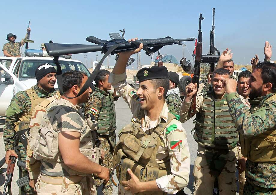 Iraqi soldiers raise their weapons as they cheer a military victory on the outskirts of the city of Tikrit. Photo: Ahmad Al-rubaye, AFP / Getty Images