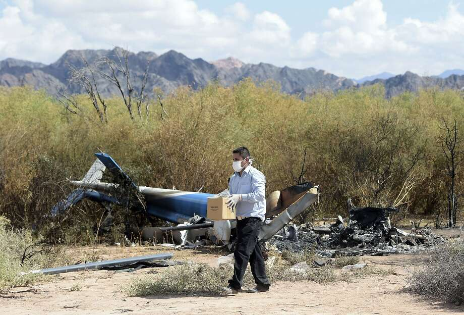 A man works amid the wreckage of two helicopters which collided in the northern Argentine province of La Rioja. The crash killed 10 people including French sports stars participating in a reality TV show. Photo: Juan Mabromata, AFP / Getty Images