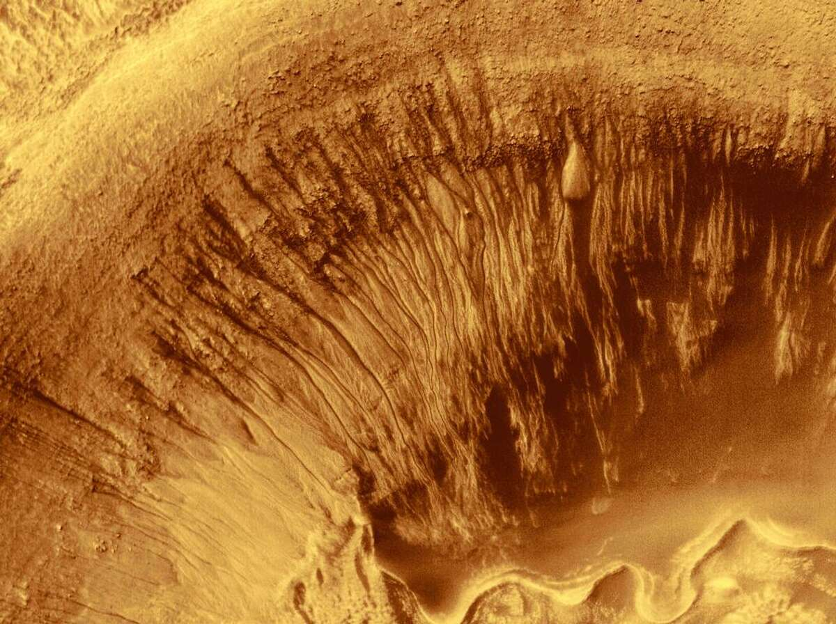 Newton Crater on Mars is a large basin formed by an asteroid impact that probably occurred more than 3 billion years ago. It is approximately 287 km (178 miles) across. The picture shown here highlights the north wall of a specific, smaller crater located in the southwestern quarter of Newton Crater. The crater of interest was also formed by an impact; it is about 7 km (4.4 mi) across, which is about seven times bigger than the famous Meteor Crater in northern Arizona in North America. The north wall of the small crater has many narrow gullies eroded into it. These are hypothesized to have been formed by flowing water and debris flows.