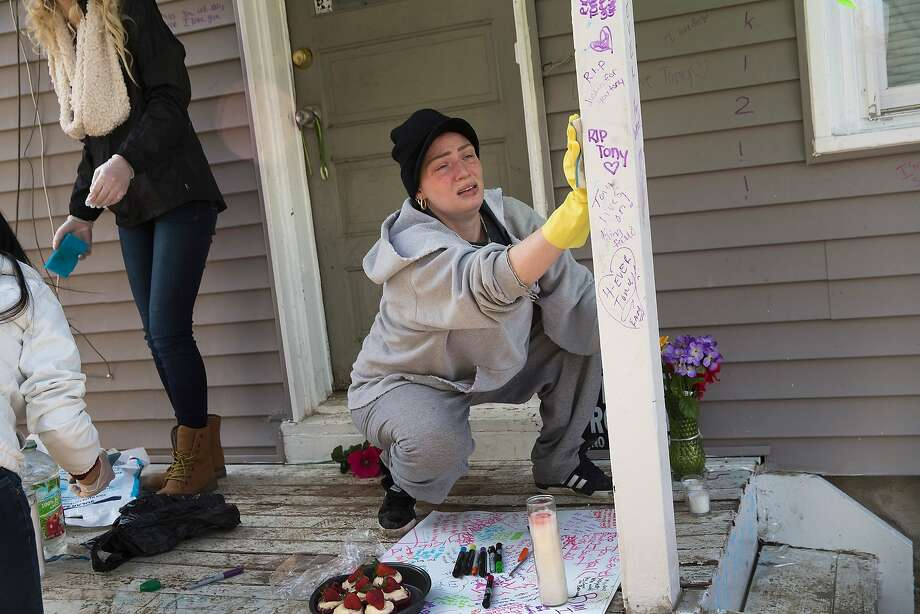 A woman scrubs blood from the porch outside the home where 19-year-old Tony Robinson was shot and killed on March 10, 2015, in Madison, Wis. Robinson was shot by Madison Police Officer Matt Kenny during a confrontation on March 6. His death has sparked several days of peaceful protests in the city. Photo: Scott Olson, Getty Images