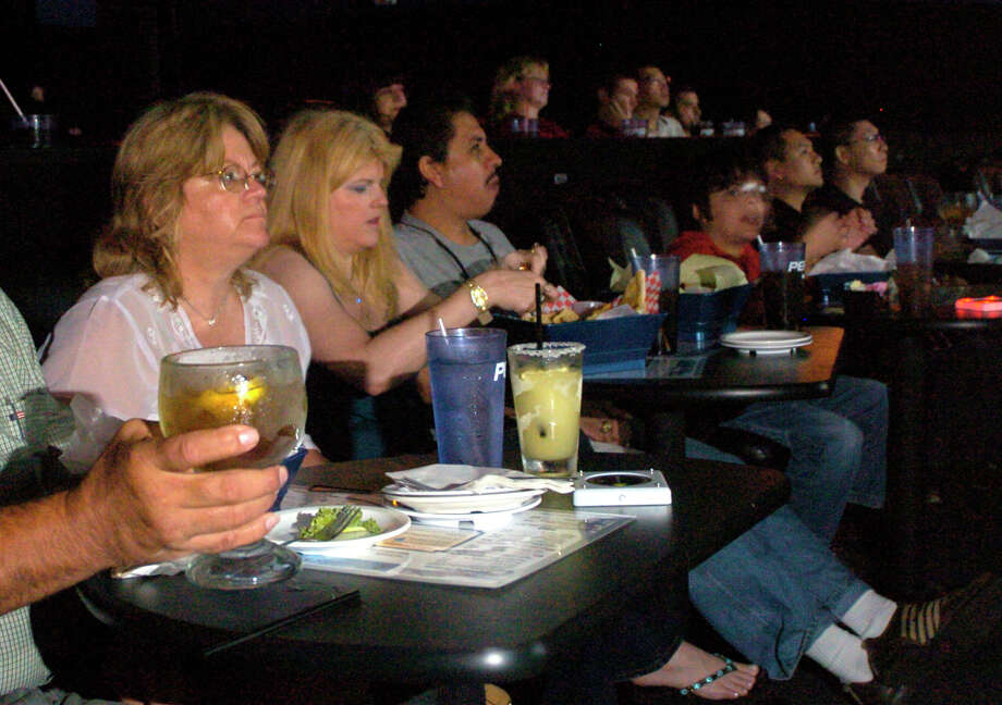 Movie Goers Eat While Watching A Film At Studio Movie Grill In West Houston.