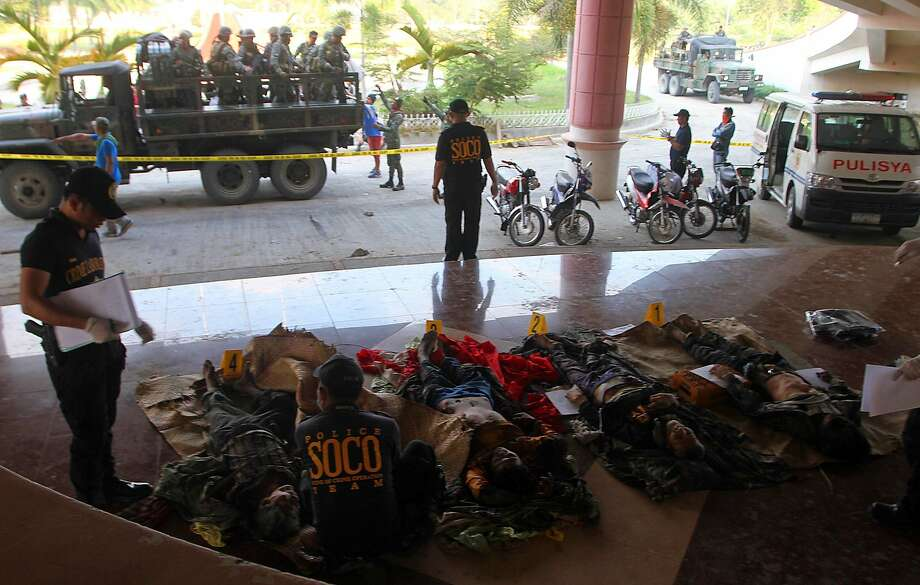 Police investigators examine the bodies of Bangsamoro Islamic Freedom Fighters in the southern island of Mindanao, after clashes with soldiers. Photo: Mark Navales, AFP / Getty Images