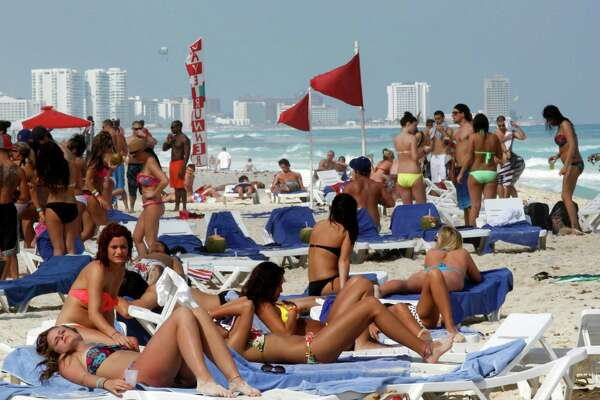 People hang out on the beach during spring break in Cancun, Mexico. The beach resort remains a top destination for American spring-breakers seeking an escape from winter. Viva Aerobus began offering nonstop flights between Houston and Cancun in December.  (AP Photo/Israel Leal, File)