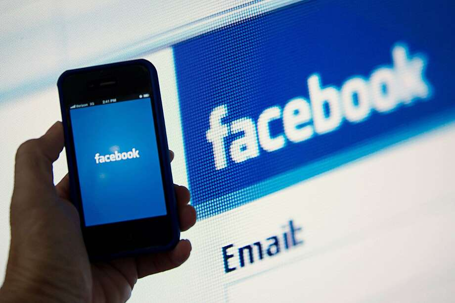 (FILES) --  In this May 10, 2012 file photo, a view of and Apple iPhone displaying the Facebook app's splash screen in front of the login page on a computer are shown in Washington, DC.  A Paris court ruled on March 5, 2015 that US-based social media site Facebook can be judged in France, in a case brought by a French user whose Facebook account was blocked by the company after he posted a photo of Courbet's painting to promote a television program on the painter. AFP PHOTO / KAREN BLEIERKAREN BLEIER/AFP/Getty Images Photo: Karen Bleier, AFP / Getty Images