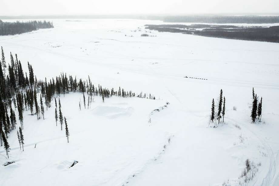 A musher makes their way down the Tanana River between Fairbanks and Nenan, Alaska, during the Iditarod Trail Sled Dog Race, Monday, March 9, 2015. Iditarod mushers began their 1,000-mile trek across Alaska along a new route Monday after poor trail conditions forced organizers to push the race's start north, bypassing a mountain range. (AP Photo/Alaska Dispatch News, Loren Holmes) Photo: Loren Holmes, Associated Press