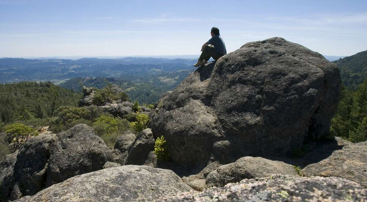 A hiker takes in the view from from Overlook Rock along the Palisades Trail in Robert Louis Stevenson State Park, along the Palisades Trail with the town of Calistoga and the Napa Valley below.