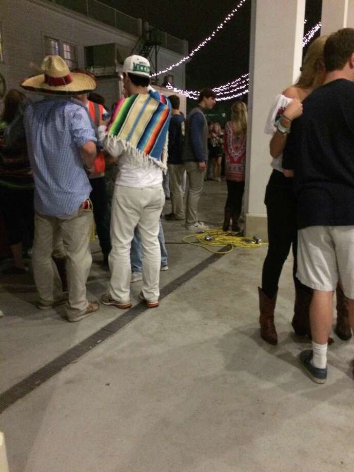 "A fraternity at the University of Texas at Austin is taking heat for hosting an alleged ""border patrol"" party at its house within spitting distance of the university campus on Saturday night.  Partygoers attending a bash hosted by UT's chapter of the national Phi Gamma Delta fraternity, known as Texas Fiji, wore ponchos, sombreros and construction gear while others wore military camoflauge outfits near photo cutout boards of people in traditional Mexican garb, a bar painted to look like a Mexican flag and a giant cutout of Patrón tequila, The Daily Texan reported. Photo: Julia Brouillette/The Daily Texan"