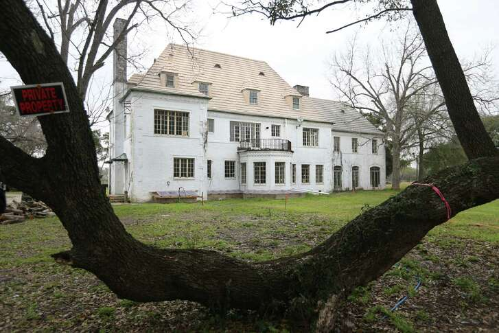 An old oak tree frames the Weingarten Mansion from the south side of the property in Riverside Terrace on Friday, Feb. 27, 2015, in Houston. ( Mayra Beltran / Houston Chronicle )