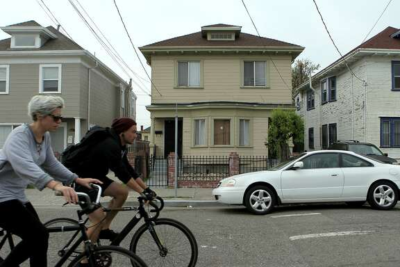 Bicyclists pass the home of Chyemil Pierce, Tuesday, March 10, 2015, in Oakland, Calif. Pierce, 30, a Kaiser employee, was slain and two other people were wounded when a gun battle erupted on the 2800 block of Chestnut Street yesterday afternoon.
