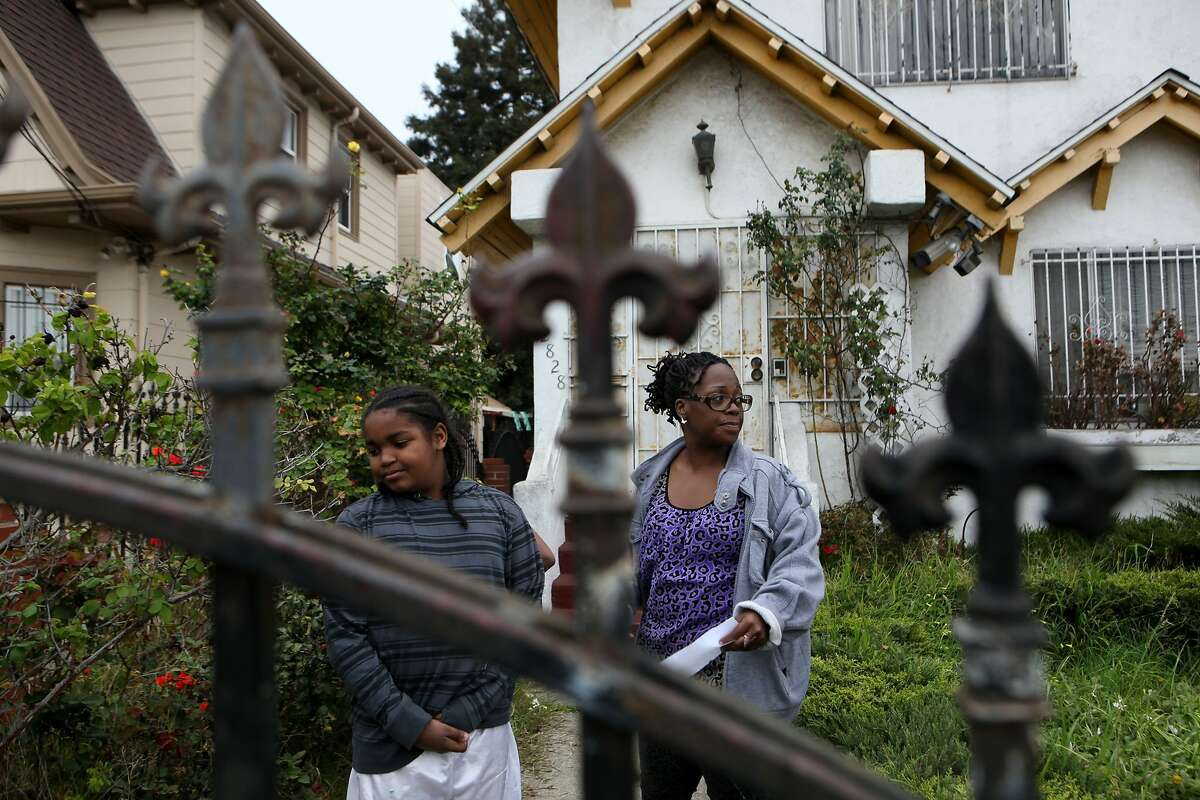Sha Blue (right) and a family member look around across the street from Chyemil Pierce's home, Tuesday, March 10, 2015, in Oakland, Calif. Pierce, 30, a Kaiser employee, was killed and two other people were wounded when a gun battle erupted on the 2800 block of Chestnut Street yesterday afternoon.