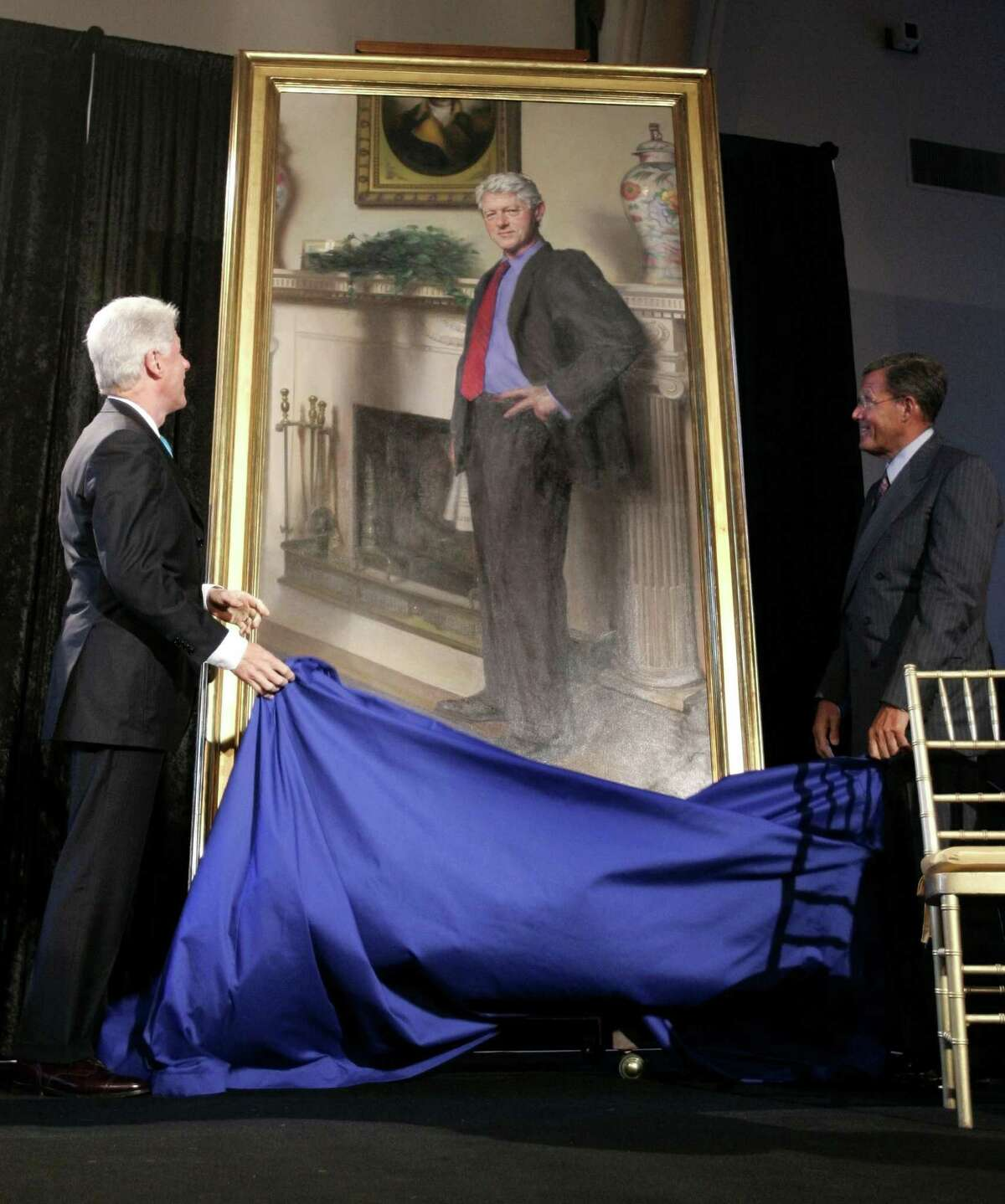 This file photo shows former President Bill Clinton, left, looking up at his portrait which is now in storage at the Smithsonian Institution. A Philadelphia artist says that his museum portrait of former President Clinton contains a shadow reference to Monica Lewinsky's infamous blue dress.
