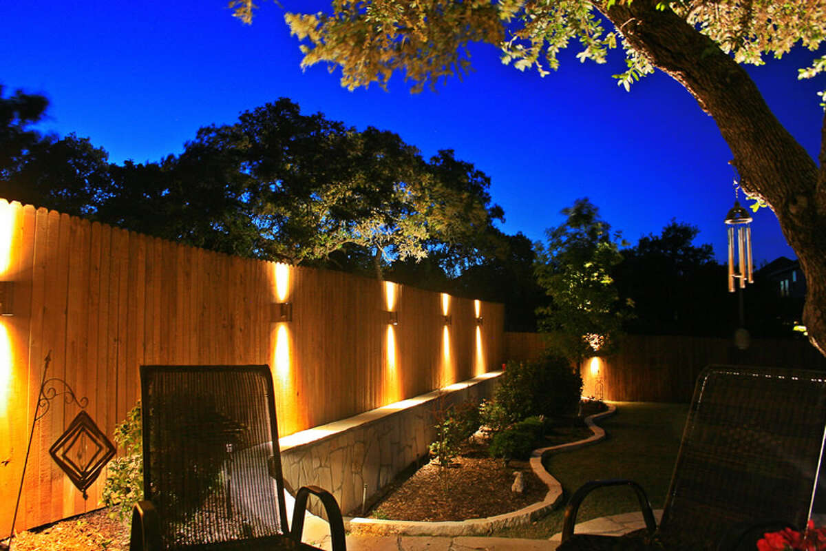 Illuminated sconces add interest and draw the eye to a fence in a design by Bolt Outdoor Lighting.