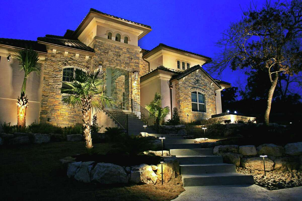 Lights wash the facade of a house, highlighting its architectural detail in a design by Bolt Outdoor Lighting.