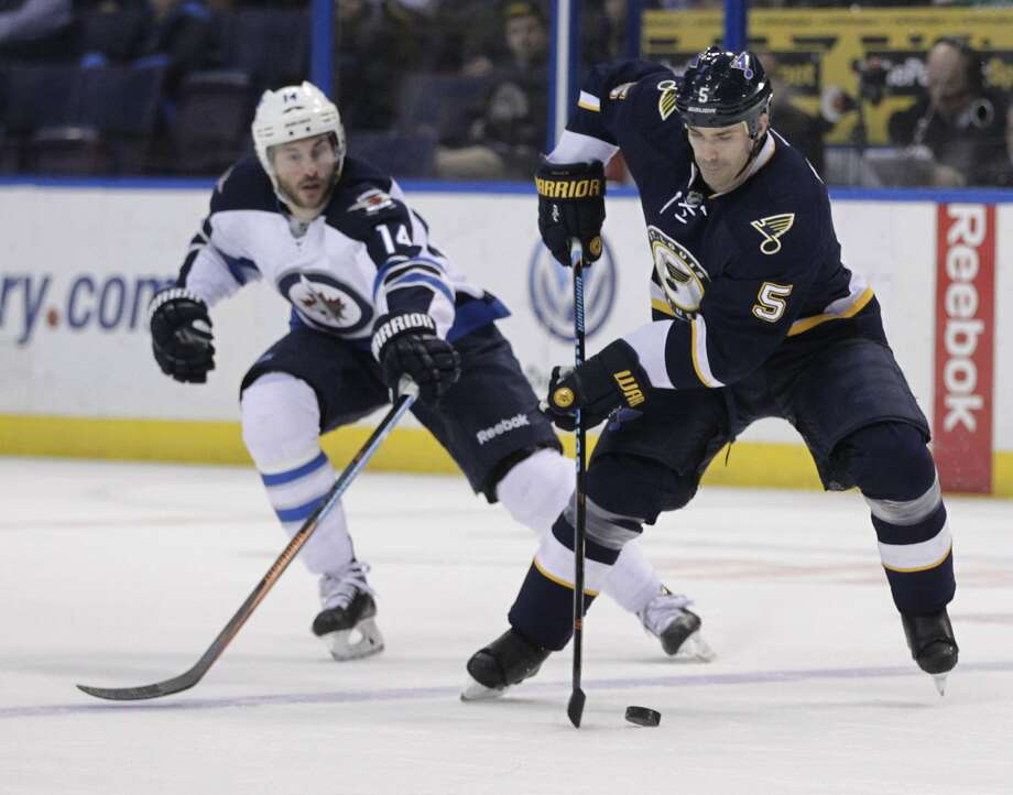 St. Louis Blues' Barret Jackman (5) controls the puck as Winnipeg Jets' Anthony Peluso (14) defends during the first period of an NHL hockey game, Tuesday, March 10, 2015, in St. Louis.(AP Photo/Tom Gannam) Photo: Tom Gannam, Associated Press