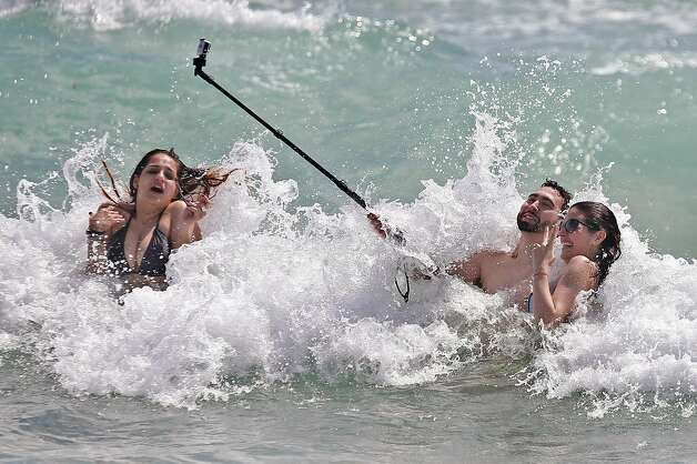 FIU spring breaker Miguel Irias, 22, holds a selfie stick as he videos his friends in the surf, Valerie Rincon, 22, left and Jennifer Perez, 22, at righ
