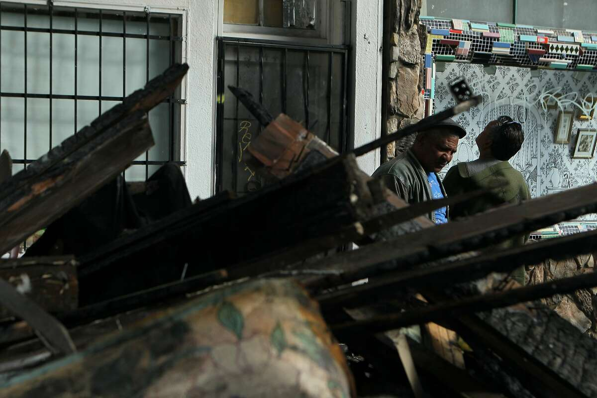 Local residents Javier Gonzalez (left) and Gustavo Solano check out the damage done to Maurices Corner Liquor at 24th Street and Treat Avenue following a 2-alarm fire, Wednesday, March 11, 2015, in San Francisco, Calif. At least four residents in the building were seriously injured.