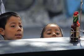Allan Rios, 6, and his 5-year-old sister Lizbeth watch chef Gerard Nebesky prepare large pans of paella at the 6th annual San Francisco Street Food Festival on Folsom Street in San Francisco, Calif. on Saturday, Aug. 16, 2014.