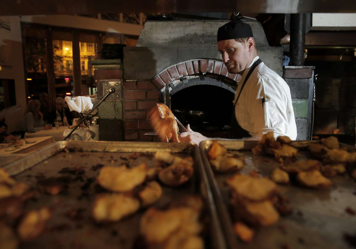 Jason Vincent pulls the roasted chicken from the oven during dinner at Zuni Cafe in San Francisco, Calif., on Tuesday, March 10, 2015. Zuni is an icon in the San Francisco dining scene, and has stayed much the same for the past 35 years, including through the death of its chef/owner Judy Rogers in late 2013.