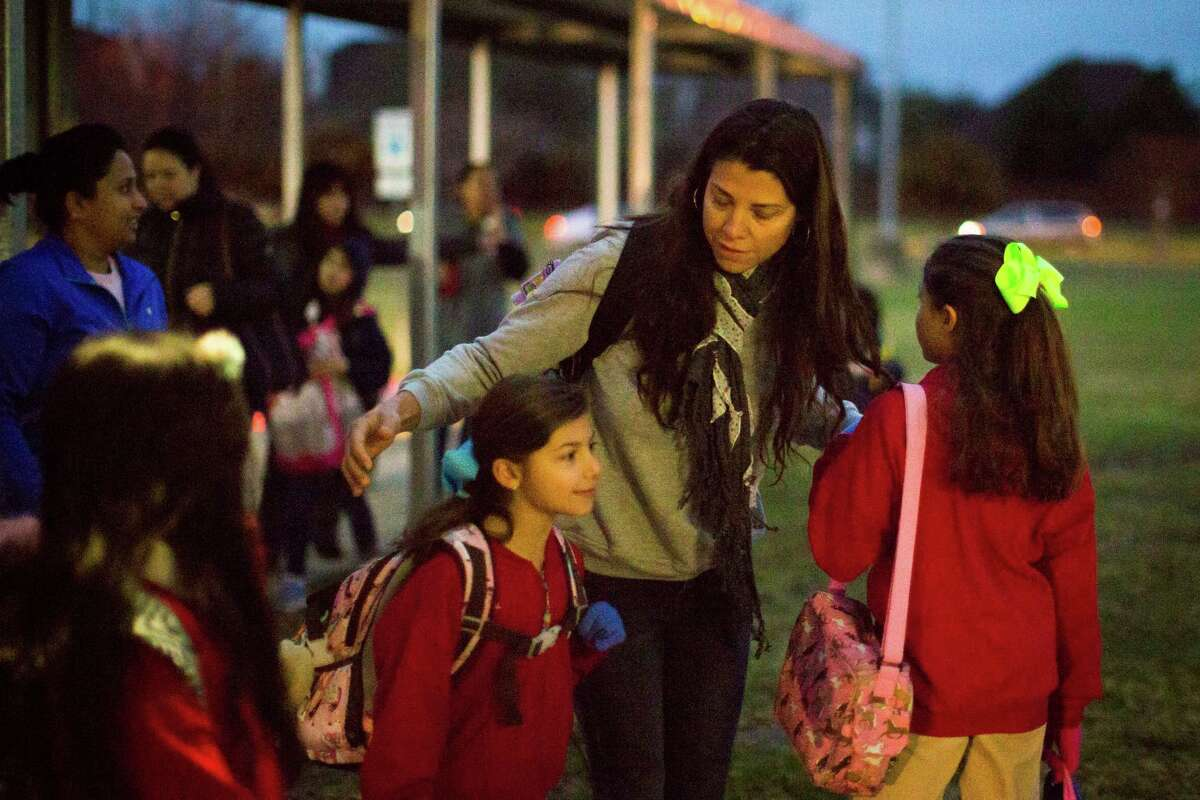 Alexandra Erkal, says good bye to her daughters Alexa Erkal, 8, and Andrea Erkal, 10, after walking them to the Barbara Bush Elementary School along with other neighborhood children who study at the same school. Wednesday, March 11, 2015, in Houston.