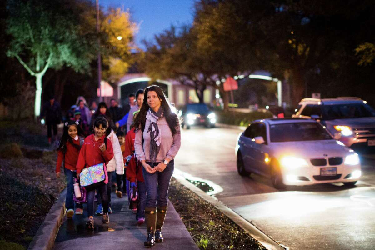 Alexandra Erkal leads the neighborhood children and their parents as they make their morning walk to the Barbara Bush Elementary School, Wednesday, March 11, 2015, in Houston. Erkal is among the parents upset that HISD was proposing to rezone the children in the Lakes of Parkway neighborhood to a different elementary school, where they couldn't walk to school.