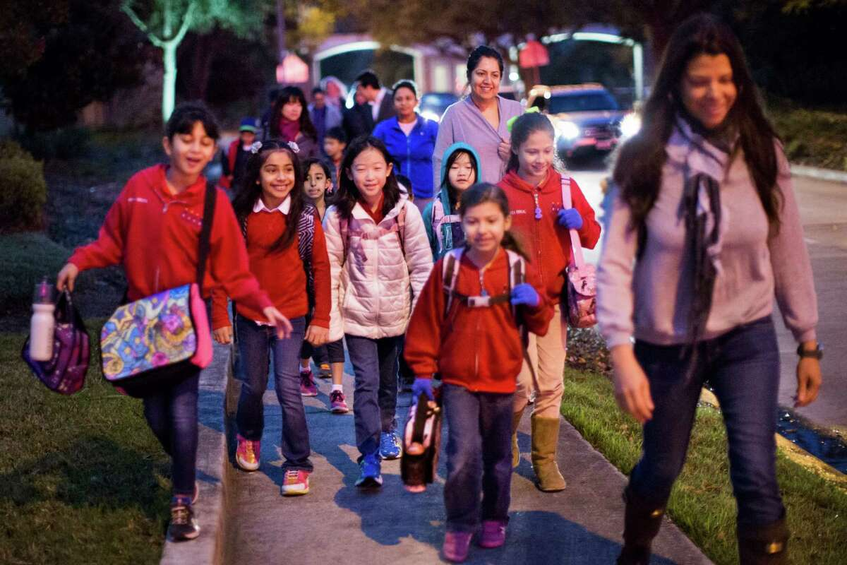 Alexandra Ramirez-Erkal, right, leads her two daughters and neighborhood children as they make their morning walk to Bush Elementary School. Erkal is among the parents upset that HISD was proposing to rezone the children in the Lakes of Parkway neighborhood to a different elementary school, where they couldn't walk to school.