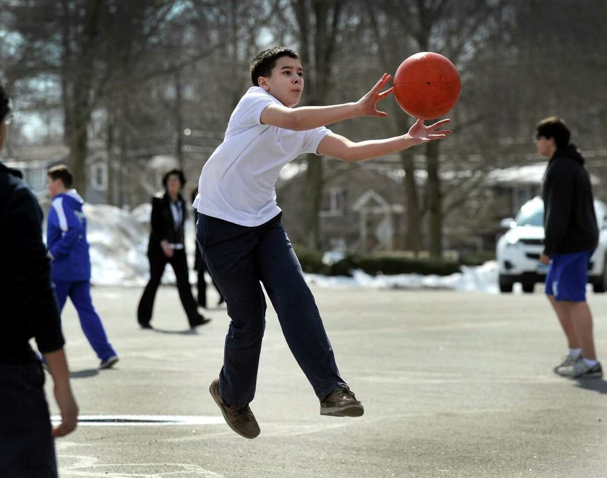 Warm enough for short sleaves, Justin Rodriguez, 12, a seventh-grader at St. Gregory the Great School in Danbury, Conn. plays dodgeball at recess Wednesday afternoon, March 11, 2015. This week is the first week the children have been outside to play in months due to this winter's very cold temperatures. Principal Mary Pitzgerald said though there's still ice and snow on the ground this week warmer weather made it time to get the kids outside.