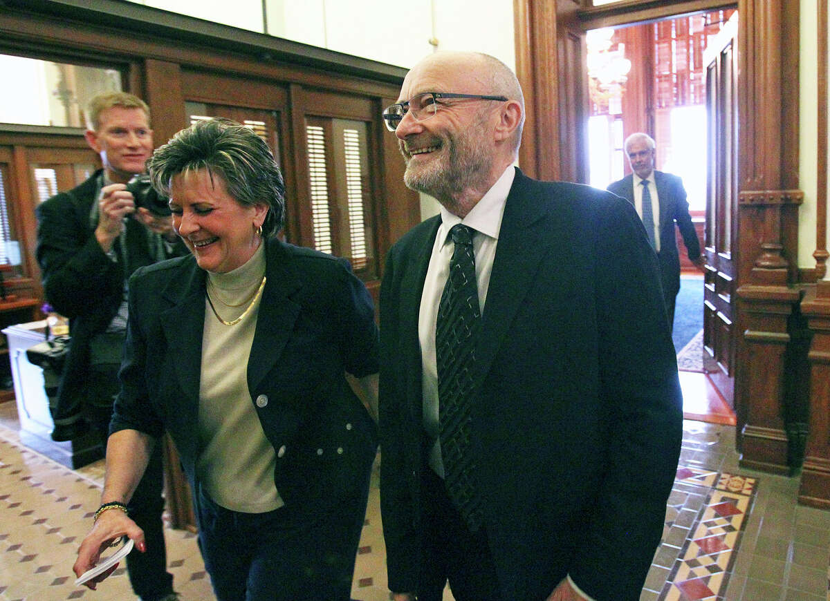 Phil Collins walks with Director of the Alamo Endowment Kaye Tucker onto the House floor to be recognized at the State Capitol as an honorary Texan on March 11, 2015.