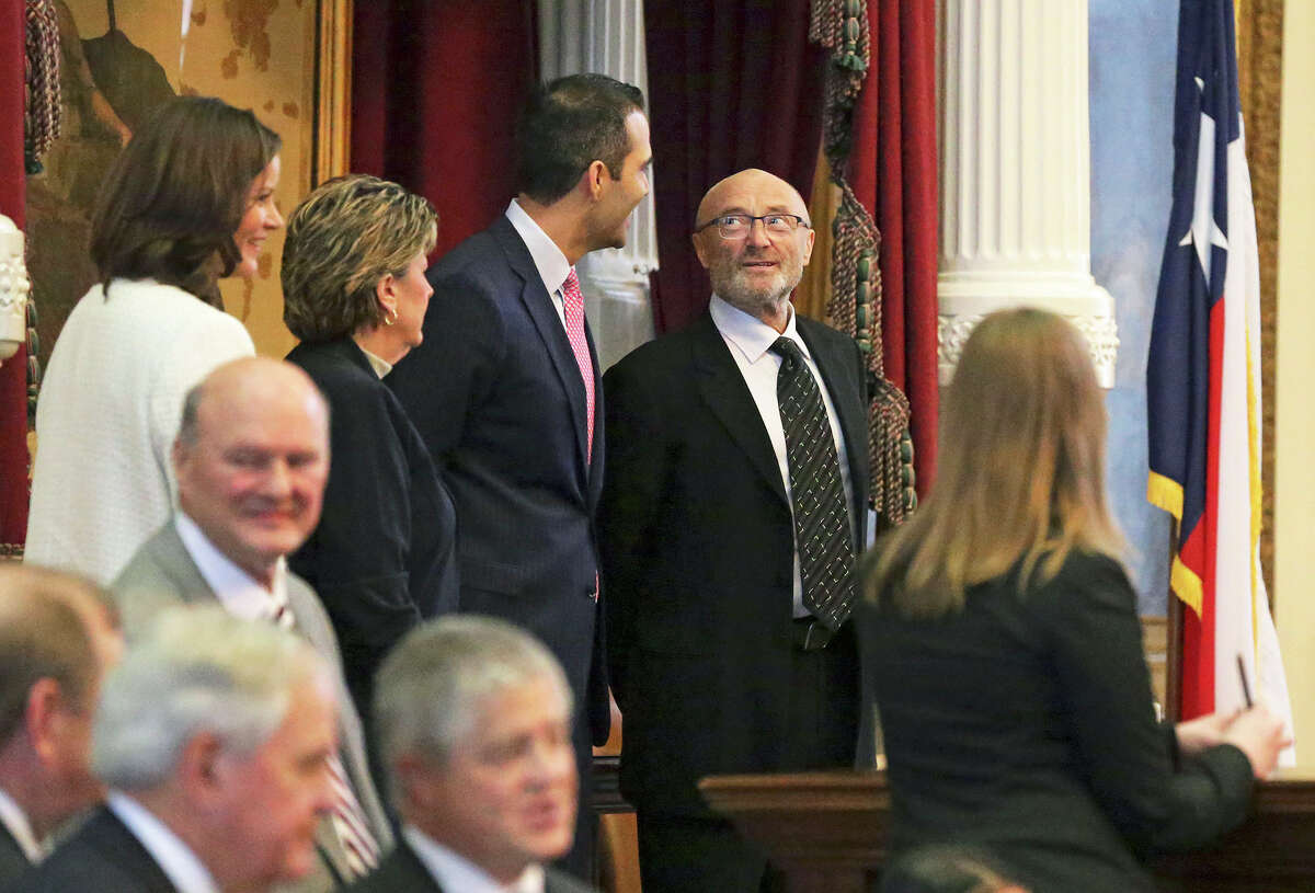Phil Collins glances at Land Commissioner George P. Bush while he is recognized in the HOuse of Representatives as an honorary Texan March 11, 2015.