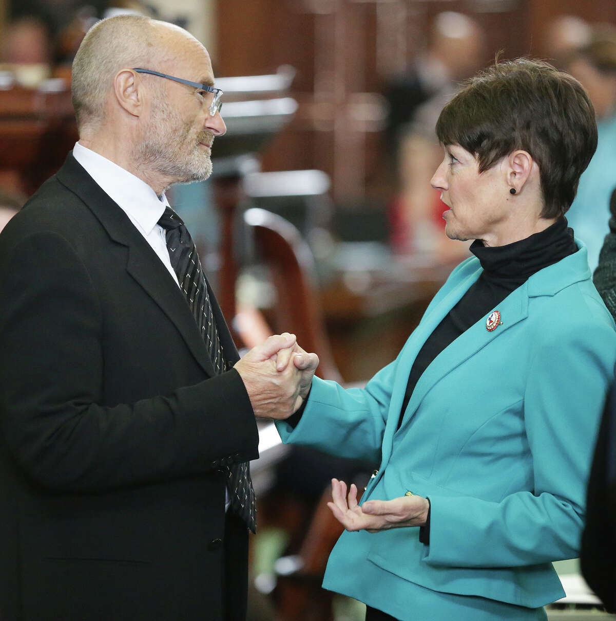 Phil Collins is greeted by Senator Dionna Campbell after he is recognized in the Senate as an honorary Texan while he visits both houses of the Legislature on March 11, 2015.